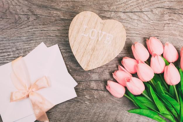 Buquê de tulipas e um envelope em um fundo de madeira