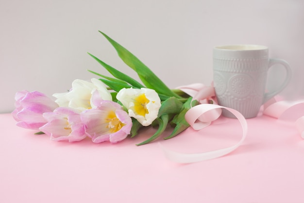 Buquê de tulipas e uma xícara de café sobre um fundo rosa pastel.