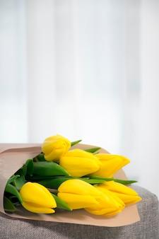 Buquê de tulipas frescas de cor amarela em uma poltrona cinza perto de uma janela no interior da casa