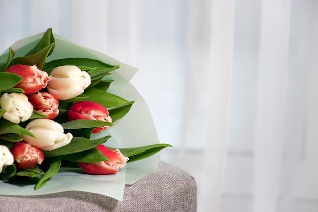 Buquê de tulipas frescas de cor vermelha e branca em uma poltrona cinza perto de uma janela de tule no interior da casa