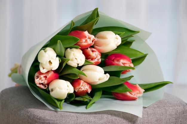 Buquê de tulipas frescas de cor vermelha e branca em uma poltrona cinza perto de uma janela no interior da casa