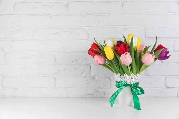 Buquê de tulipas frescas lindas coloridas na mesa contra a parede de tijolo branco