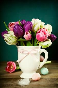 Buquê de tulipas lindas e ovos de páscoa na mesa de madeira