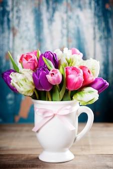 Buquê de tulipas lindas na mesa de madeira