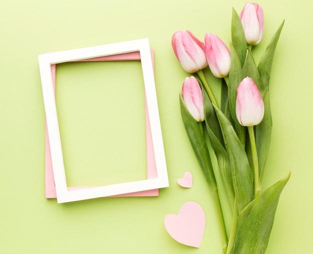Buquê de tulipas plana leigos ao lado do quadro