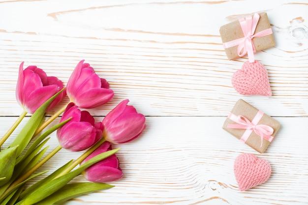 Buquê de tulipas, presentes embrulhados e corações de malha em uma madeira branca, vista superior