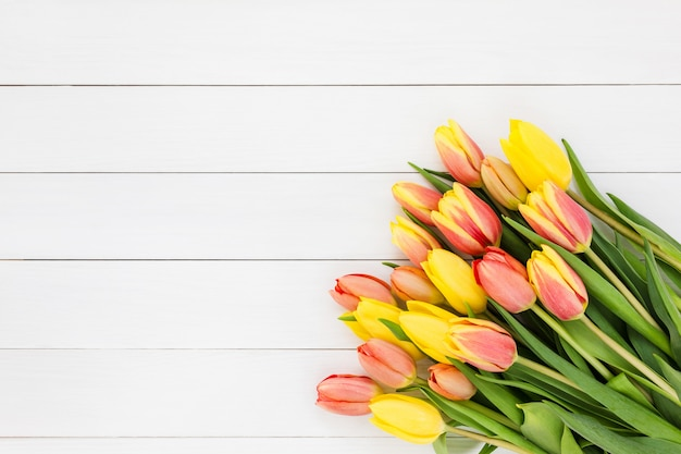 Buquê de tulipas primavera em madeira branca. vista de cima, copie o espaço