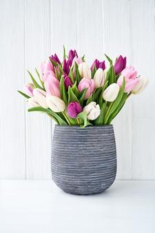 Buquê de tulipas rosa e brancas no conceito de férias em vaso cinza