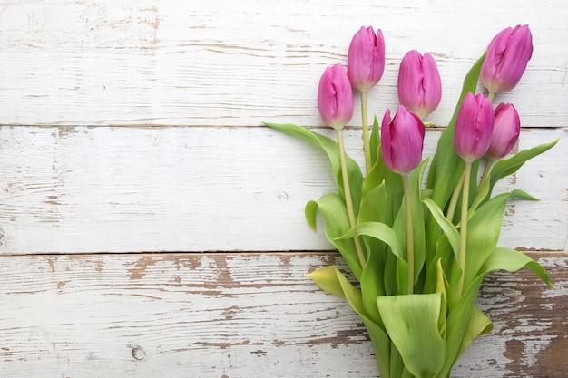 Buquê de tulipas roxas em fundo branco de madeira. vista do topo