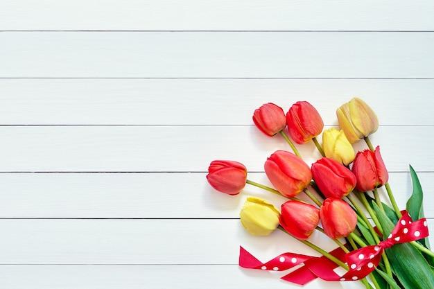 Buquê de tulipas vermelhas decorado com fita em fundo branco de madeira. copie o espaço, vista superior. dia das mães, aniversário, conceito de dia dos namorados. fundo de férias.