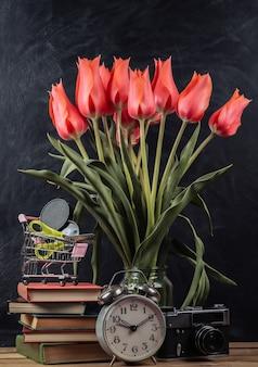 Buquê de tulipas vermelhas e acessórios de escola, câmera retro em um fundo de quadro-negro de giz. ainda vida escolar