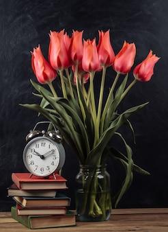 Buquê de tulipas vermelhas e pilha de livros com despertador no fundo do quadro de giz. ainda vida escolar