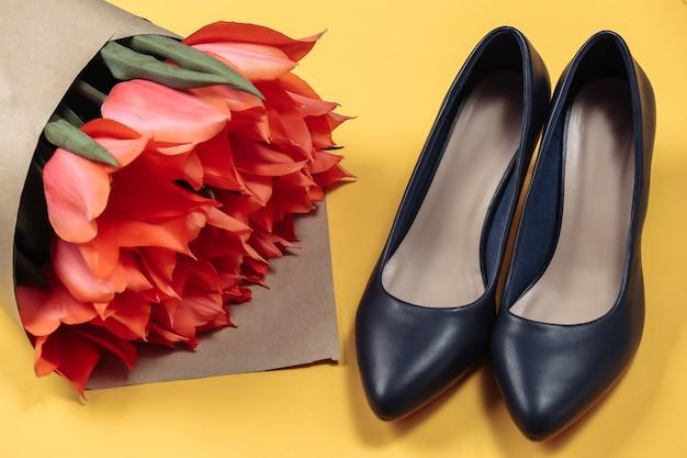 Buquê de tulipas vermelhas e sapatos de salto alto em fundo amarelo. dia das mães no feriado ou dia 8 de março, aniversário.