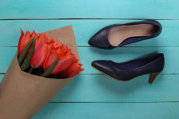 Buquê de tulipas vermelhas e sapatos de salto alto em fundo azul de madeira. dia das mães no feriado ou dia 8 de março, aniversário. vista do topo