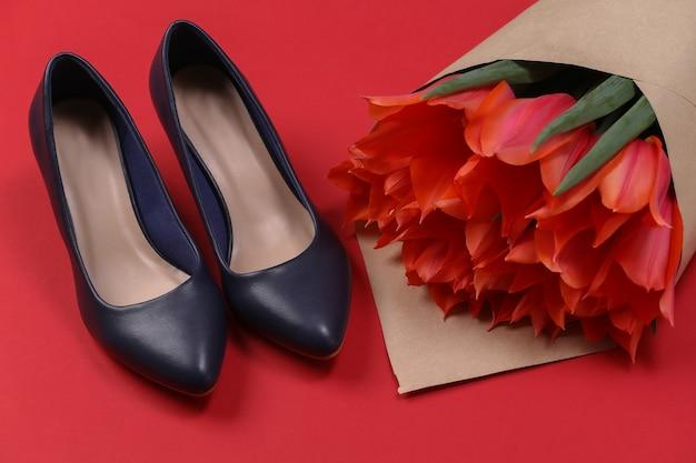 Buquê de tulipas vermelhas e sapatos de salto alto em fundo vermelho. dia das mães no feriado ou dia 8 de março, aniversário.