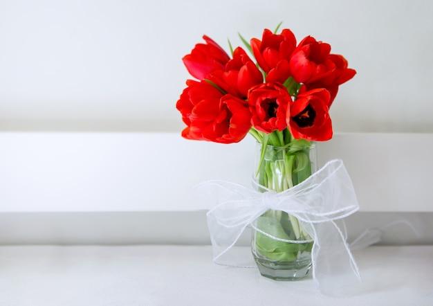 Buquê de tulipas vermelhas em um copo com gravata branca e fundo