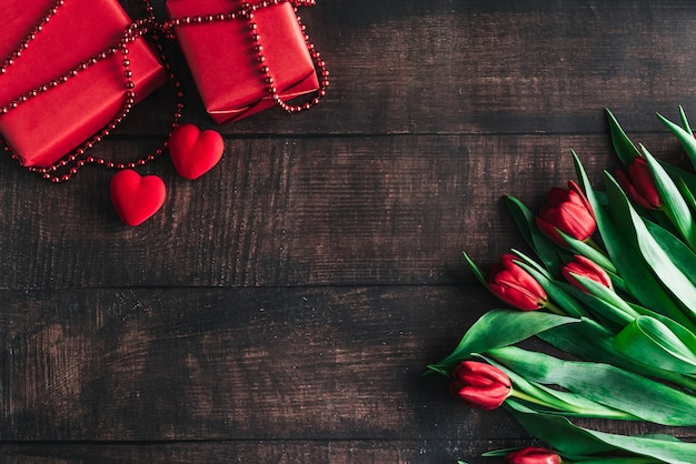 Buquê de tulipas vermelhas em um fundo de madeira com uma caixa vermelha. plano de fundo do dia das mães. dia dos namorados