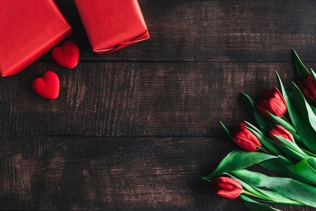 Buquê de tulipas vermelhas em um fundo de madeira. flores da primavera. plano de fundo do dia das mães.