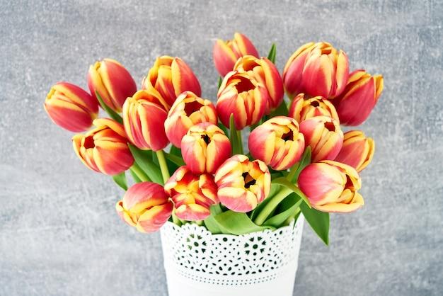Buquê de tulipas vermelhas em um vaso de flores brancas em um espaço de cópia de fundo cinza de férias