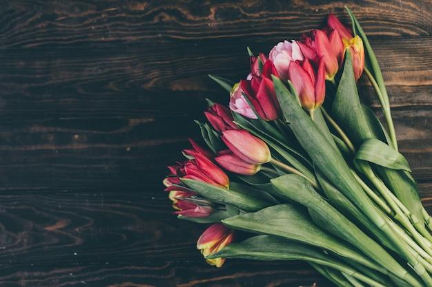 Buquê de tulipas vermelhas em uma mesa de madeira em um estilo escuro