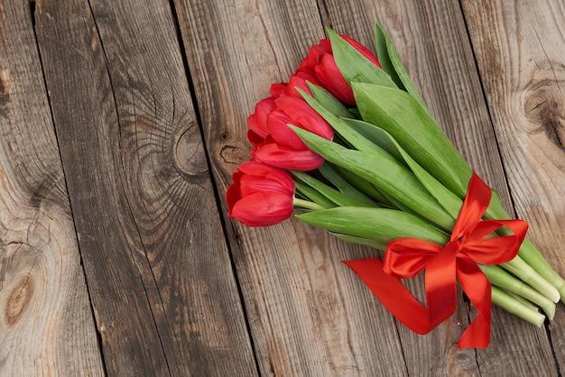 Buquê de tulipas vermelhas florescendo com hastes verdes e folhas amarradas com uma fita de seda vermelha