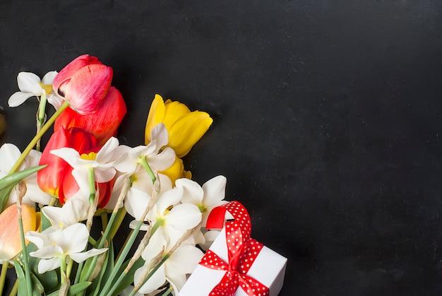 Buquê de tulipas vermelhas, narcisos e presente no preto