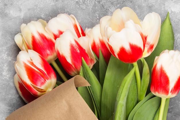 Buquê de tulipas vermelho-brancas em papel kraft, sobre um fundo claro. vista do topo.