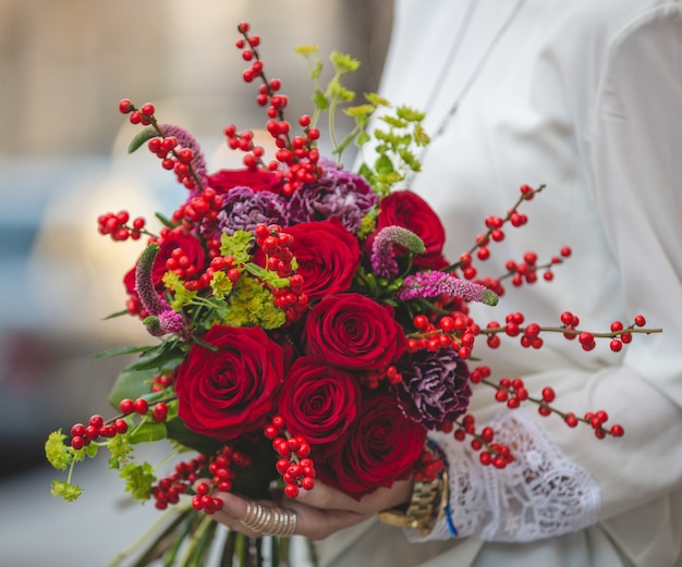 Buquê de veludo vermelho de frutas, flores e flores nas mãos de uma senhora de blusa branca
