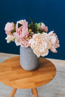 Buquê de verão de peônias rosa e corar contra o fundo da parede azul