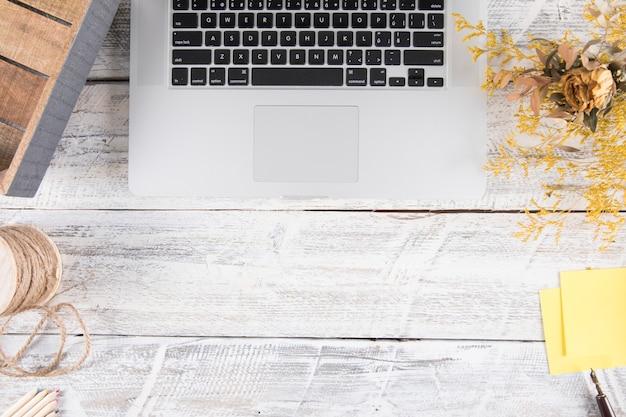 Buquê e papelaria na mesa perto de laptop