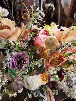 Buquê em ângulo de flores pastel coloridas, derramando sobre madeira