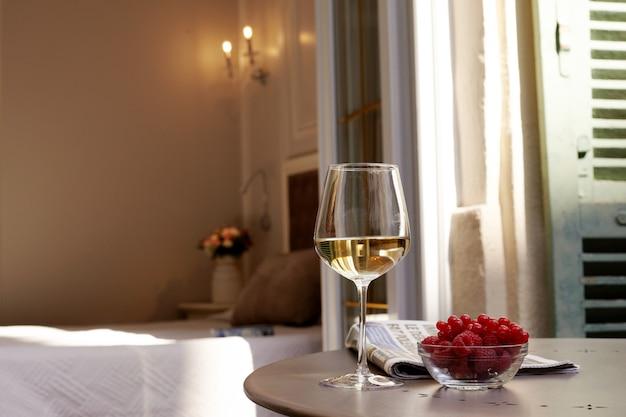 Buquê em um vaso, um copo de vinho branco e framboesas frescas em uma mesa no terraço