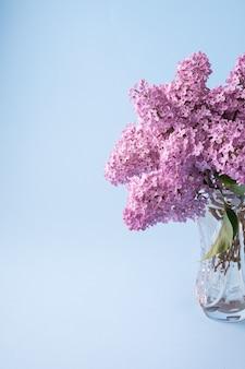 Buquê lilás florescendo em vaso de cristal transparente