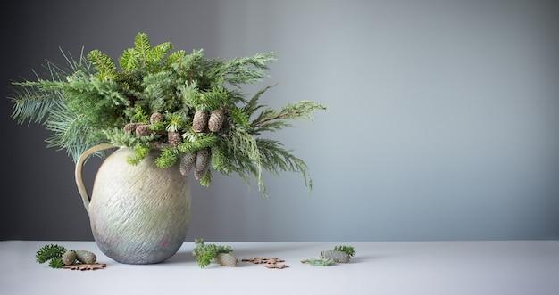 Buquê natural de natal em um velho jarro de cerâmica na parede cinza do fundo