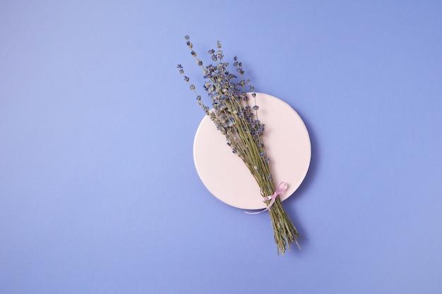 Buquê natural orgânico de lavanda seca em uma placa de cerâmica redonda com sombras suaves e espaço de cópia. vista do topo.