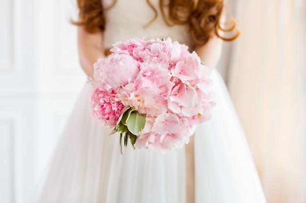 Buquê nupcial lindo de flores rosa do casamento nas mãos da noiva.