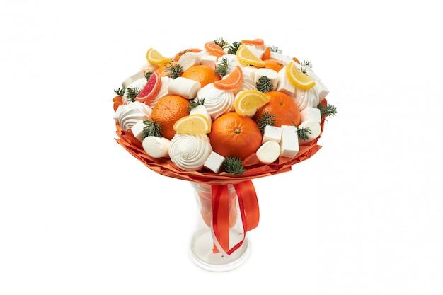 Buquê original criado a partir de marshmallows, zéfiro, marmelada e tangerinas fica em um vaso em branco