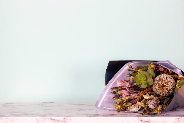 Buquê original de flores frescas na mesa de mármore na luz de fundo