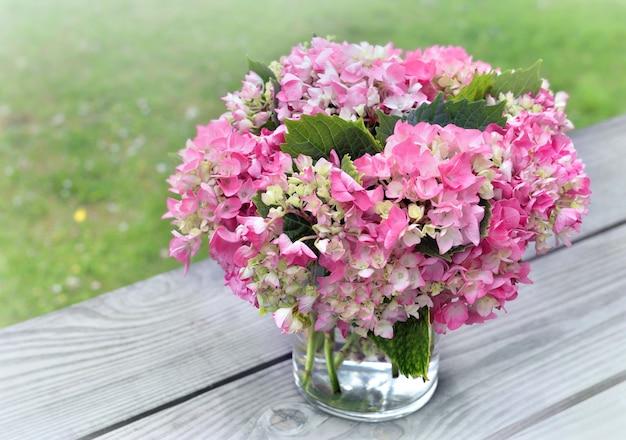 Buquê redondo romântico de hortênsia rosa em um vaso de vidro colocado sobre uma mesa no jardim