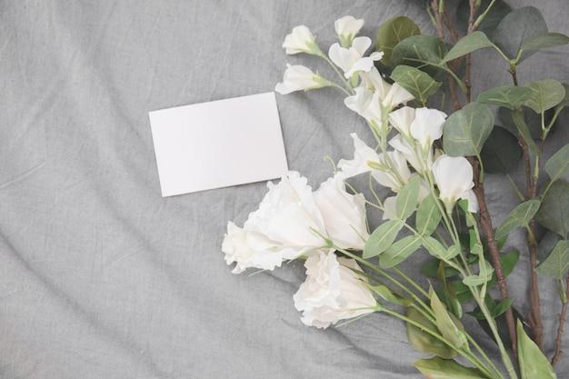 Buquê romântico de flores brancas e pilha de cartão vazio dos desenhos animados na cama.