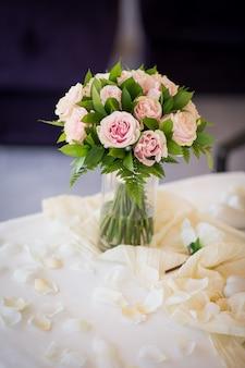 Buquê romântico de rosas cor de rosa com verde na mesa. cerimônia de casamento. vertical