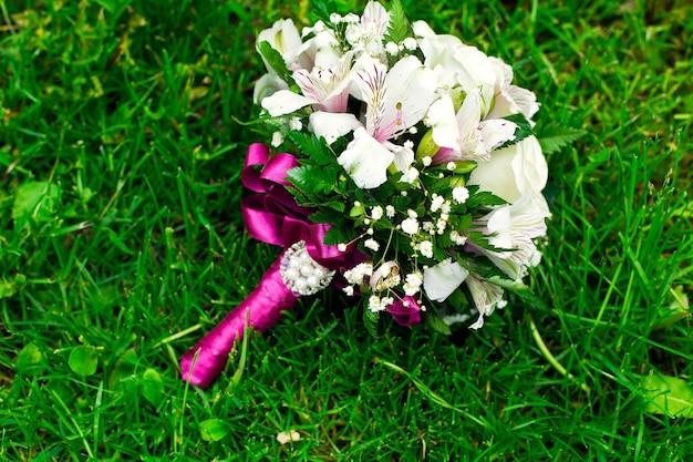 Buquê rosa e branco de flores do casamento em um gramado verde.