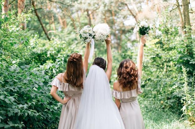 Buquês de casamento nas mãos da noiva e damas de honra. buquê de casamento branco