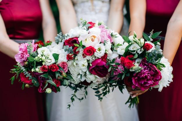 Buquês de casamento nas mãos da noiva e damas de honra. peônias roxas e rosas brancas