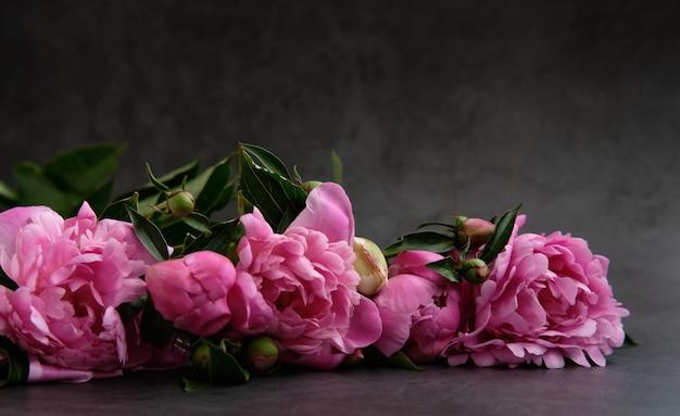 Buquês de flores de peônias rosa iluminadas pela luz em uma superfície cinza escura