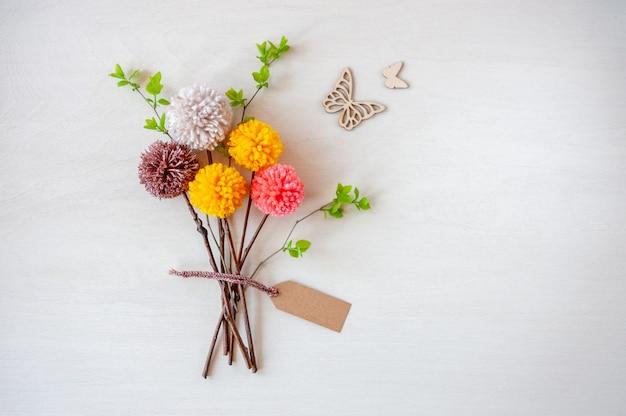 Buquês de flores feitos de pompons coloridos na mesa de madeira