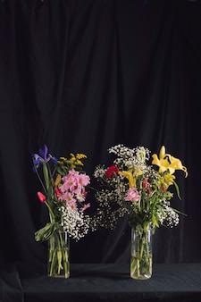 Buquês de maravilhosas flores brilhantes em vasos com água