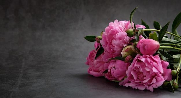 Buquês de peônias rosa iluminadas pela luz em uma superfície cinza escura