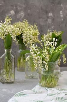 Buquês frescos de lírios do vale em vasos de vidro na toalha de mesa branca em cinza
