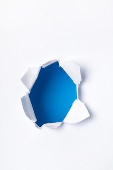 Buraco com lados rasgados em um pedaço de papel.